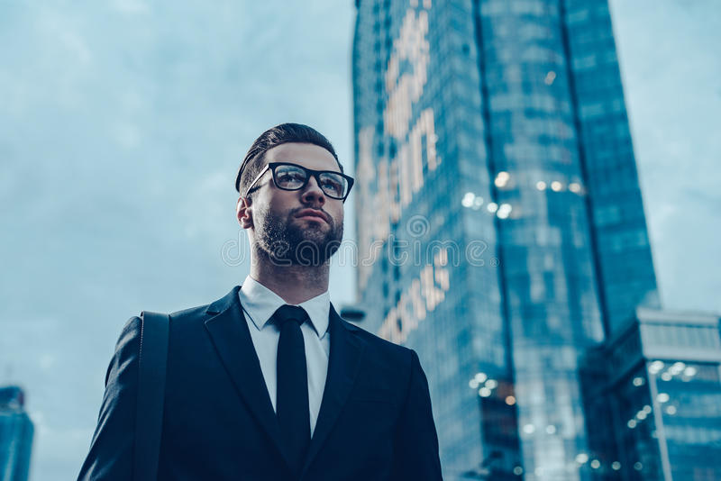 Modern businessman. Low angle view of confident young and handsome man in formalwear walking along the street with cityscape in the background royalty free stock images