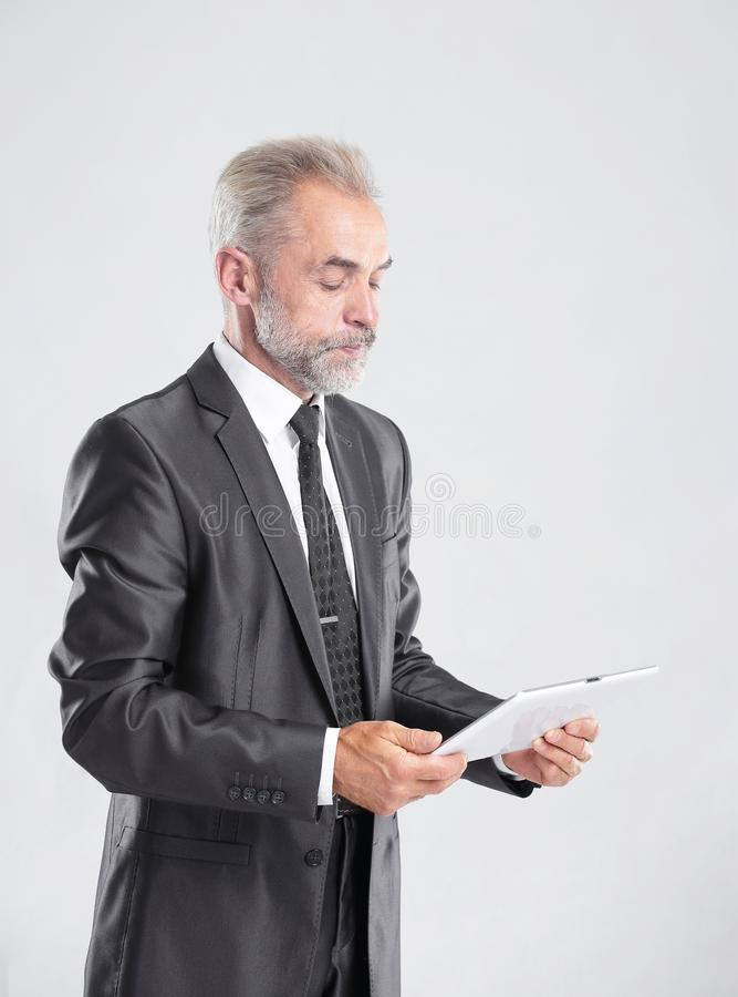 Modern businessman reading text on a digital tablet.isolated on grey background royalty free stock image