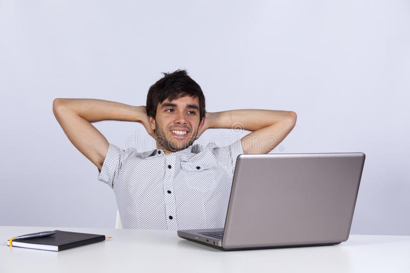 Modern businessman relaxing at his office. Young modern businessman relaxing at his office happy with his work stock images
