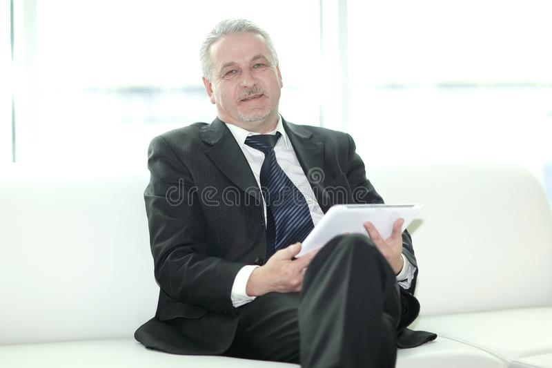 Modern businessman sitting in office lobby.people and technology.  stock photo