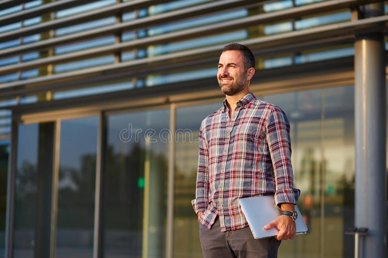 Modern businessman standing outside office. Handsome modern businessman standing outside office stock photography