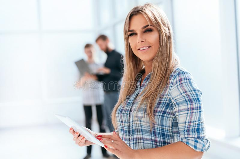 Modern businesswoman with digital tablet standing in a bright office stock photos