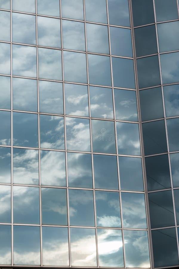 Modern byggande Glass fasad som reflekterar molnig blå himmel fotografering för bildbyråer