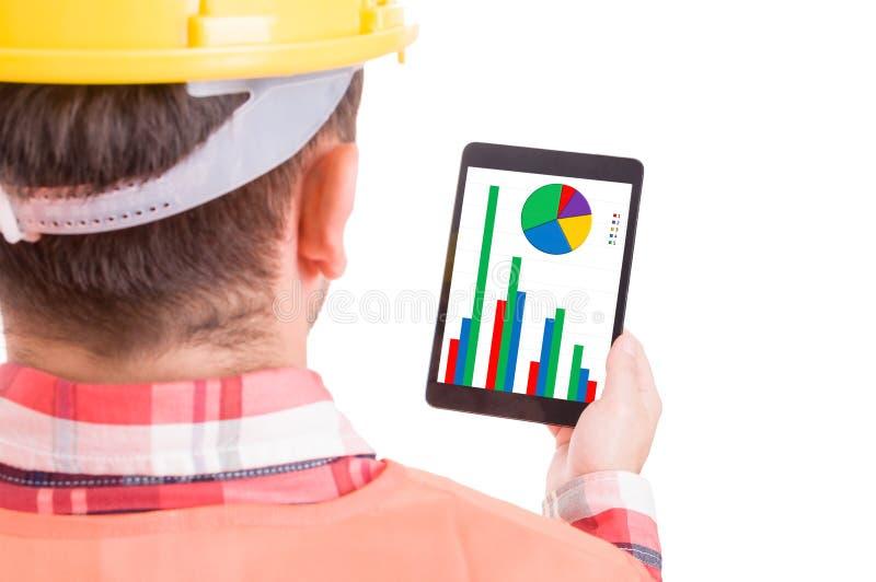 Modern byggmästare eller byggnadsarbetare som kontrollerar diagram på minnestavlan arkivfoton