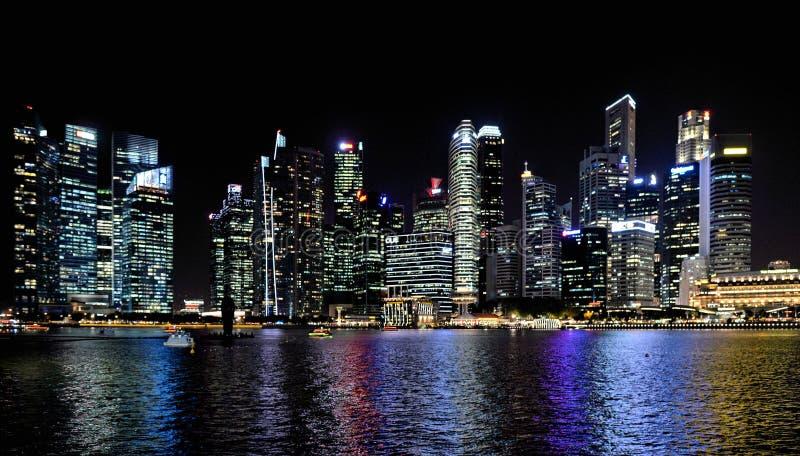 Modern byggnader och ljus på havs- och abstrakt begrepparkitekturer och natthorisont i Singapore royaltyfri fotografi