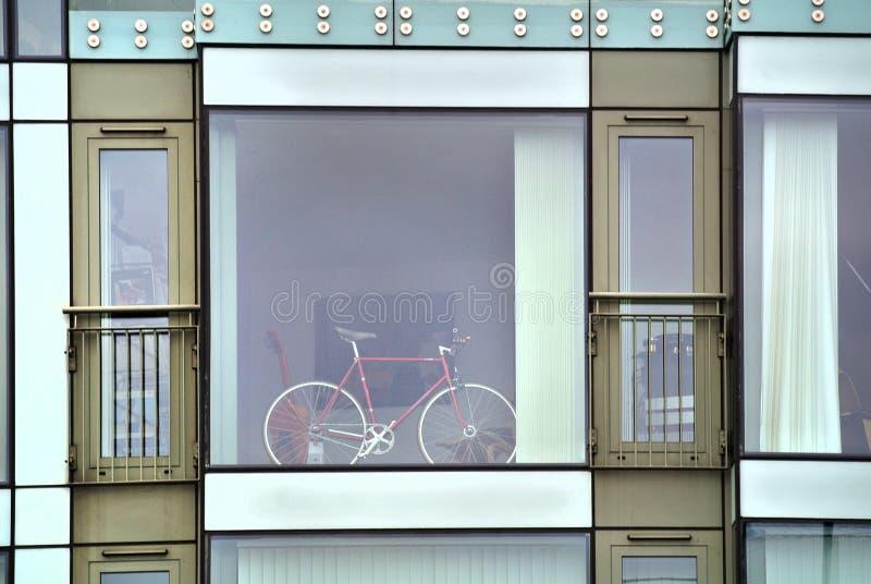 Modern byggnadsfasad med det stora fönstret och en cykel, royaltyfria foton