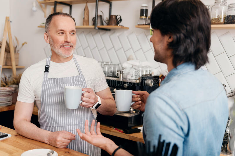 Modern cafe business. Cheerful coworkers. Portrait of two content and friendly cafe workers drinking coffee and enjoying time together while the break at coffee stock photography