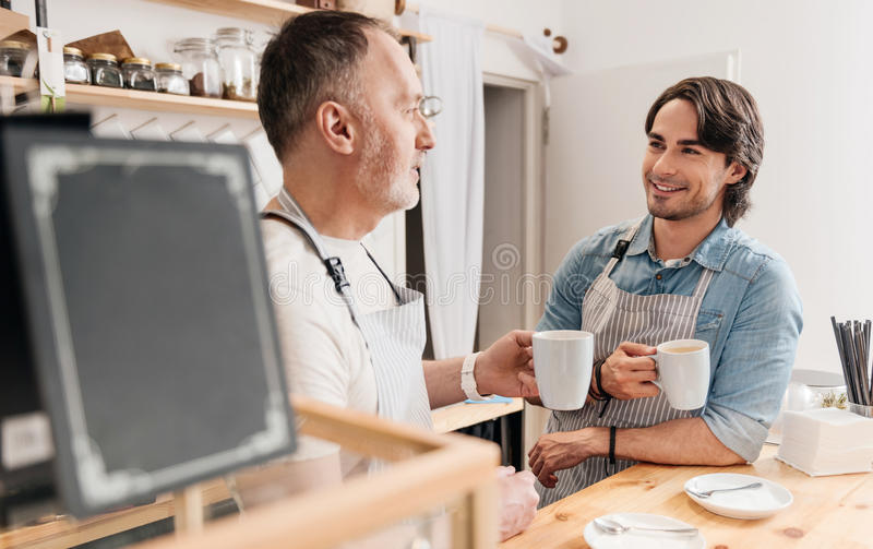Modern cafe business. Friendly atmosphere. Happy and positive cafe workers drinking coffee and communicating together while the break at coffee shop royalty free stock photos