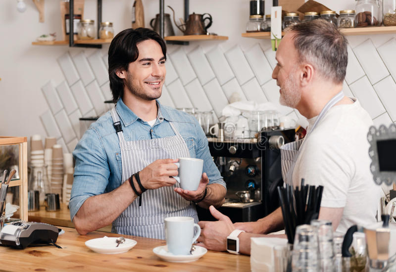 Modern cafe business. Sincere friendship. Content and cheerful cafe workers holding cups and drinking coffee, communicating together while the break at stock photography