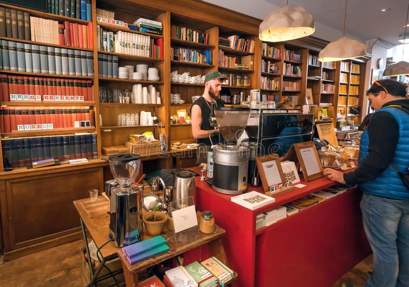 Modern cafe inside old bookstore with readers and people buying snacks for breakfast royalty free stock photography