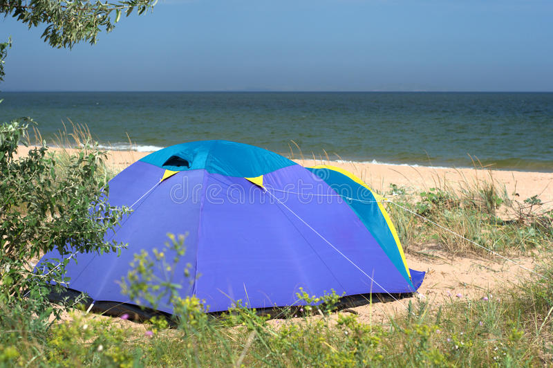 Modern camping tent on the sea shore. Blue and purple camping tent standing on sand seashore. Drought tolerant grass are growing around. Clear sky and blue green royalty free stock photography