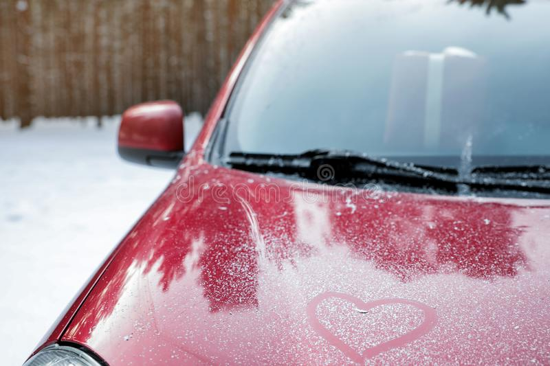 Modern car with drawn heart on hood in snowy winter forest, closeup. Space for text royalty free stock photography