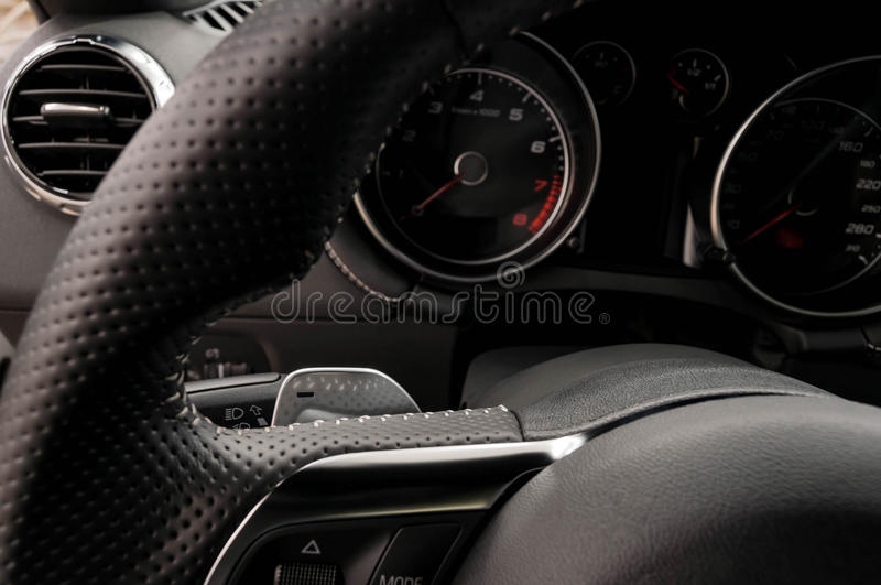 Modern car gear lever. Paddle on car's steering wheel. Interior detail stock photography