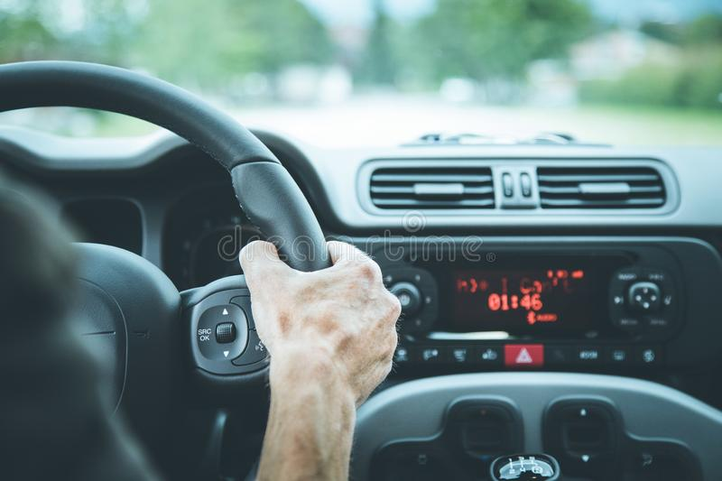Modern car interior: Male hands on a sports car steering wheel. Sports car steering wheel, male hands steering, interior, dashboard, driving, sporty, instruments royalty free stock photos