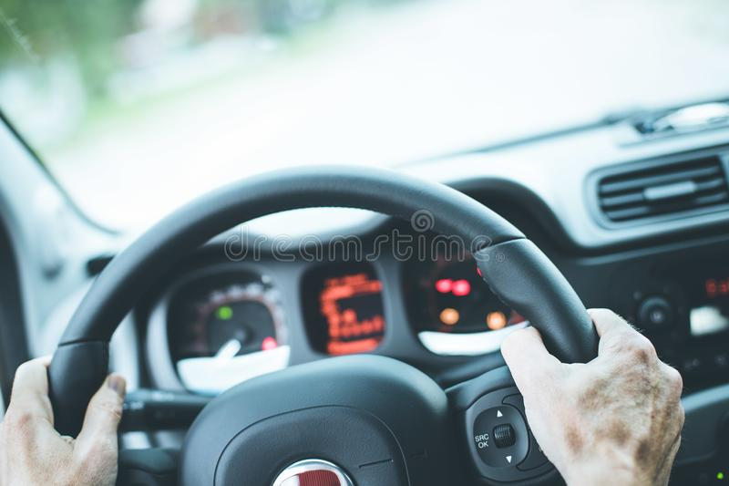 Modern car interior: Male hands on a sports car steering wheel. Sports car steering wheel, male hands steering, interior, dashboard, driving, sporty, instruments royalty free stock image