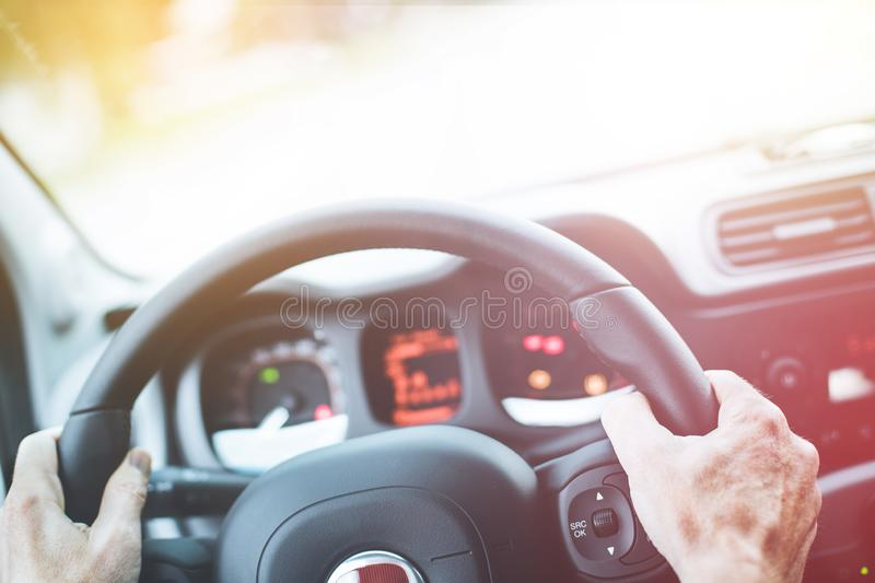 Modern car interior: Male hands on a sports car steering wheel. Sports car steering wheel, male hands steering, interior, dashboard, driving, sporty, instruments royalty free stock photography