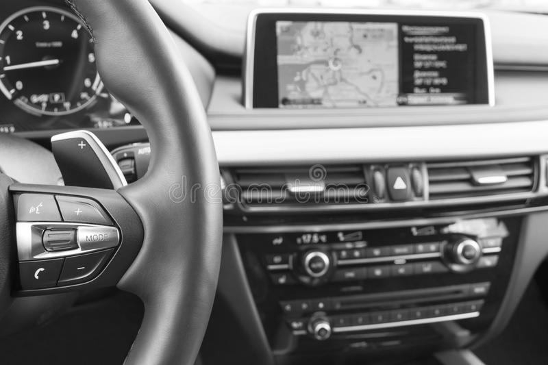 Modern car interior, steering wheel with media phone control buttons, navigation, screen multimedia system background. Car interior details. Black and white stock photo