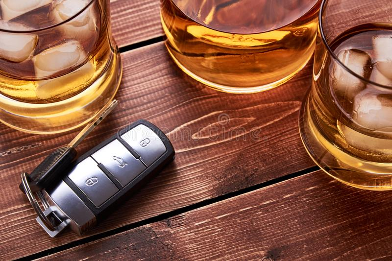 Modern car keys on wooden table top in bar. Glass and bottle of whiskey or other alcohol with ice. for the article on drunk. Modern car keys on wooden table top royalty free stock photos