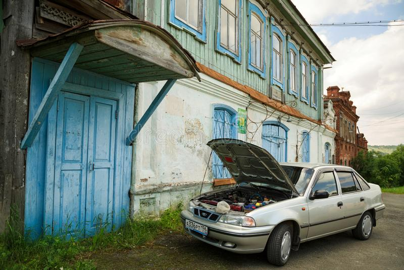 Modern car parked in front of the historical building. Village of Visim, Sverdlovsk region, Russia. VISIM, RUSSIA - JUNE 27, 2015. Modern car with an open hood royalty free stock images