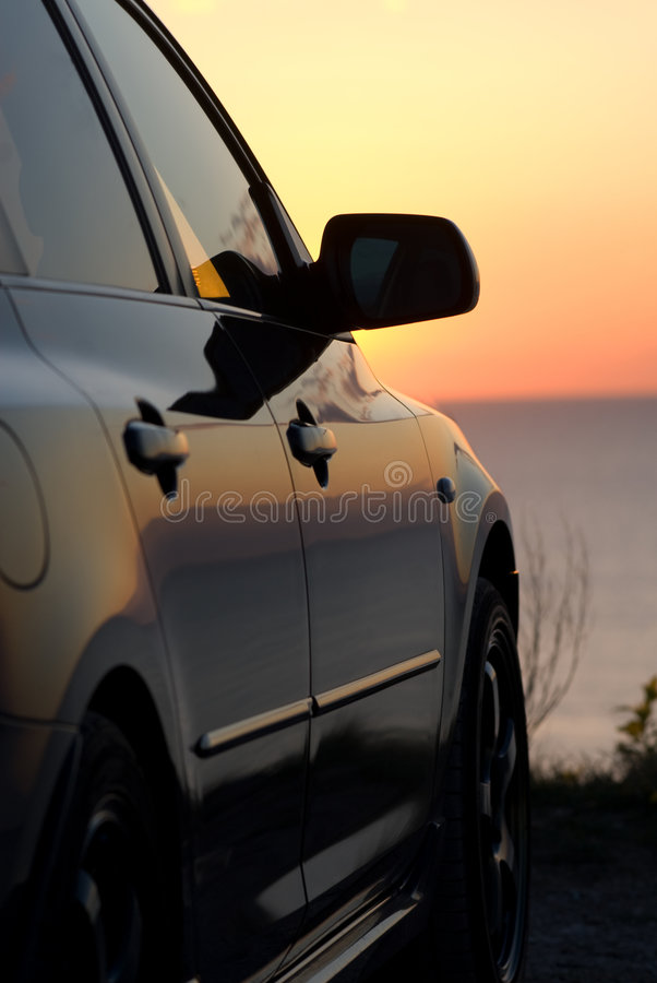 Modern car at sunset. The right side of a modern car and sunset over sea or ocean in the background stock photography