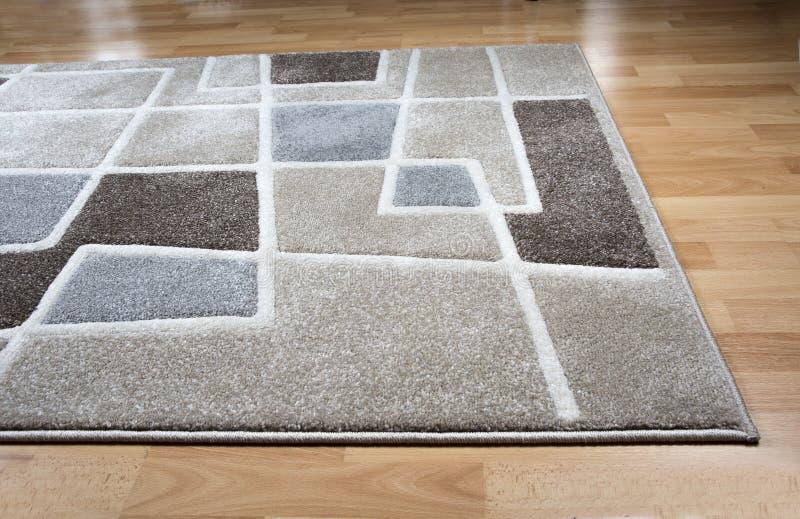 Modern carpet on laminate parquet floor stock image
