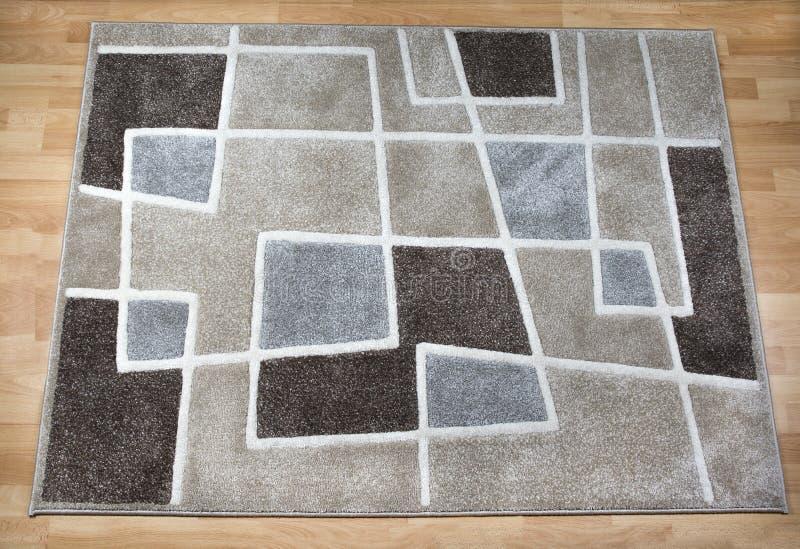 Modern carpet on laminate parquet floor stock photos