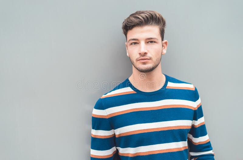 Modern and casual. Handsome young man isolated on gray background stock images