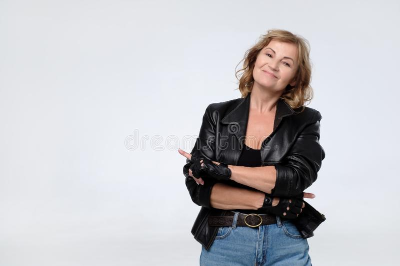 Woman pointing left and smiling broadly while looking at camera smiling. stock image