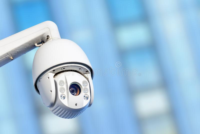 Modern CCTV camera with business buildings in the background. Close-up of modern CCTV camera with business buildings in the background stock photos
