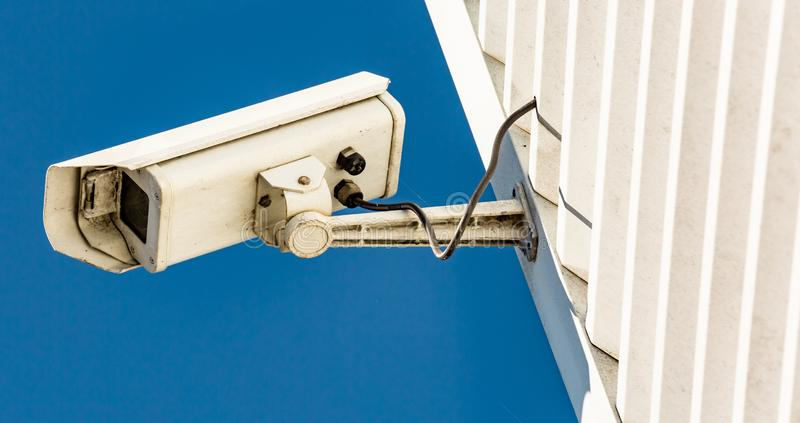 Modern CCTV camera on the wall of an industrial building. Close-up of modern CCTV camera on the wall of an industrial building stock photos