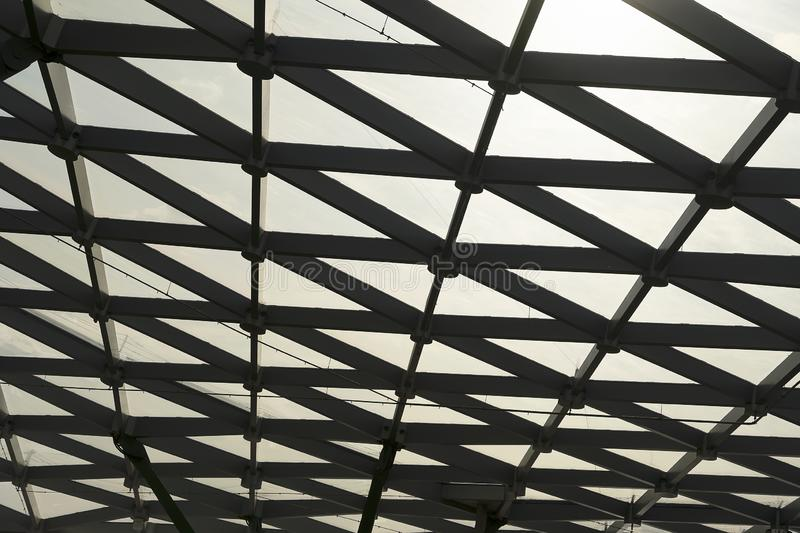 Modern ceiling with glass elements, metal mesh with green grass. Futuristic metal and glass roof royalty free stock photo