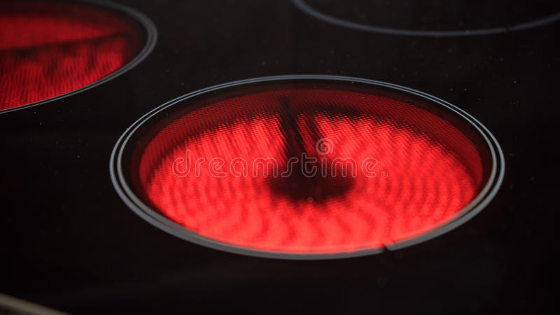 Modern ceramic cooktop. A close up view of a modern ceramic cooktop showing the two heating elements turned on stock photos