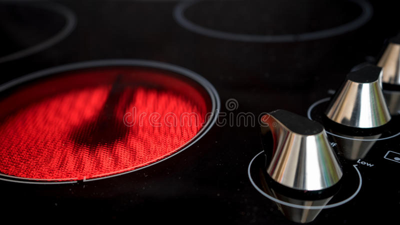 Modern ceramic cooktop. A modern ceramic cooktop showing the control knobs and one heating element turned on stock photography