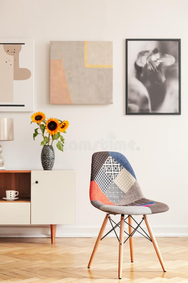 Modern chair in white apartment interior with posters above cupboard with sunflowers. Real photo. Concept stock photo