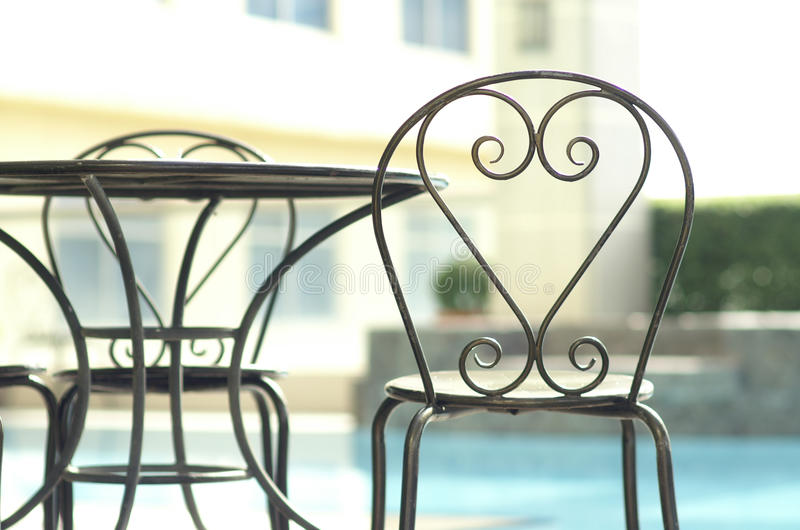 Modern chairs beside pool stock photography