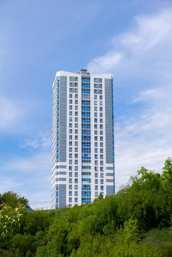 Modern cheap multi-storey apartment building. On top of a hill against the sky stock images