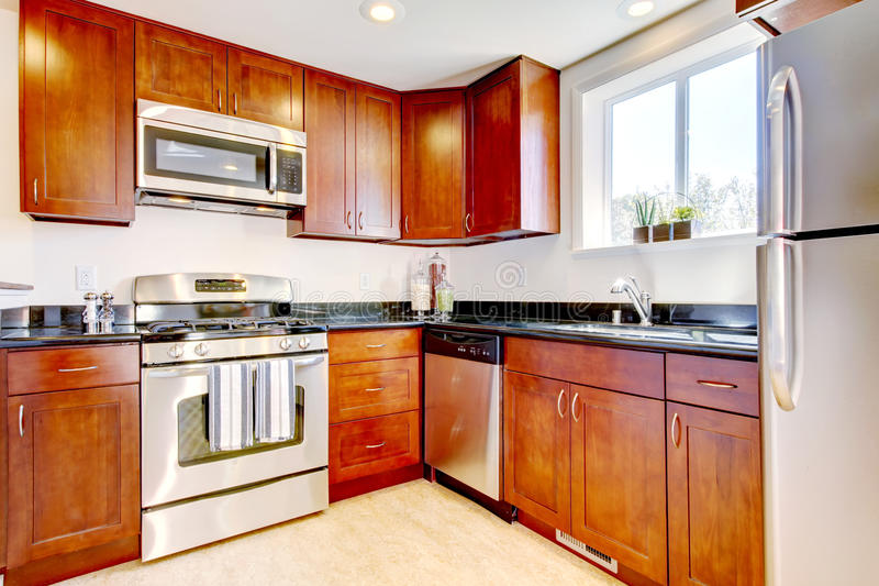 Modern cherry kitchen with steal appliances. Modern new cherry kitchen with steal appliances royalty free stock images