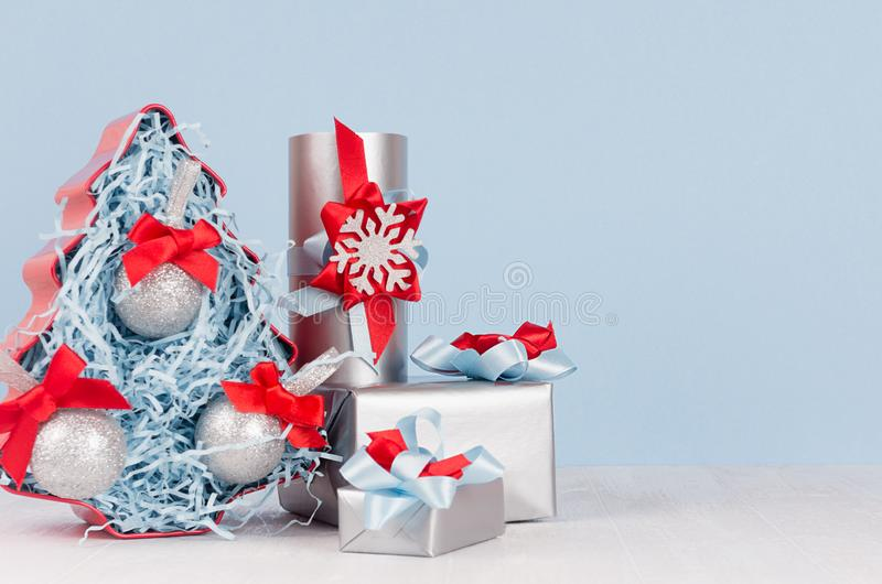 Modern christmas background in light pastel blue and silver color - decorative fir tree with balls and various gift boxes with red. And blue ribbons and bows on stock images