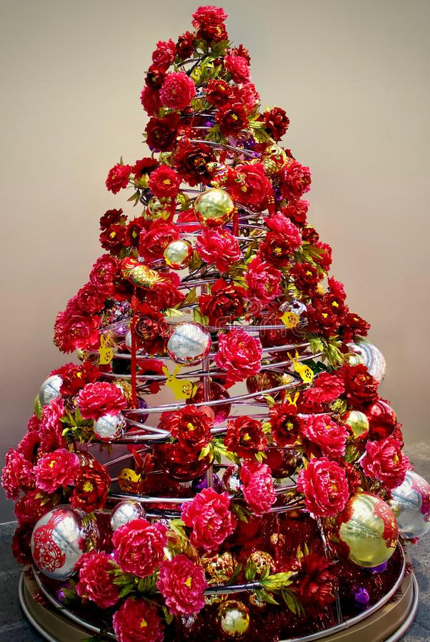 Modern christmas tree of red flowers. Scarlet peons, golden rabbits and shiny balls. Christmas and New Year stock image
