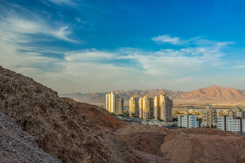 Modern city building from desert sand stone mountain rocks Israeli Middle East landmark urban view in bright colorful summer time. Day blue sky background space royalty free stock photography