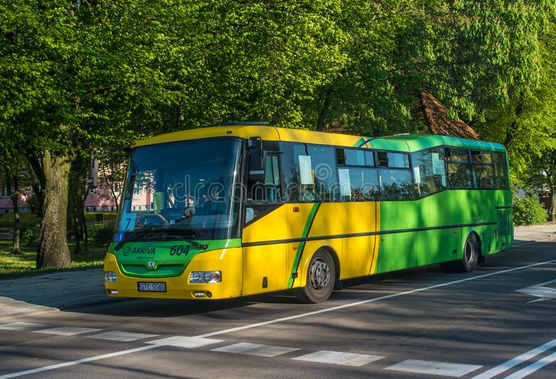 Modern city bus driving in Elblag, Poland. Modern city bus in Elblag, northern Poland, used for public transpirt in this city. Yellow and green colors on chassis royalty free stock image