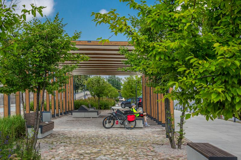Cyclist resting on a bench on a walkway. Modern city, Cyclist resting on a bench on a walkway royalty free stock photos