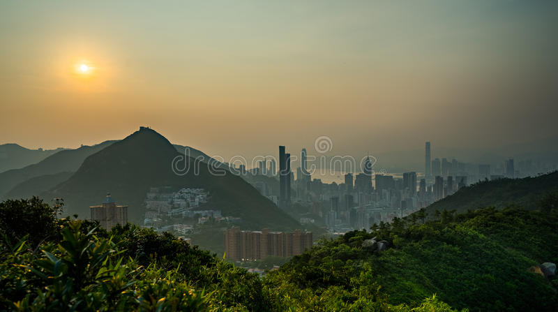 Modern city next to mountain in sunset stock photography