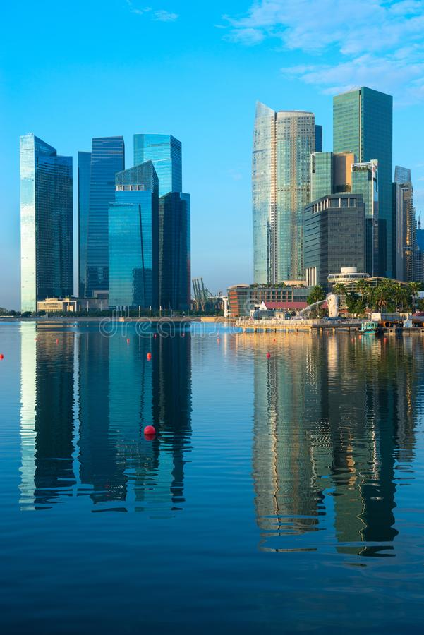 Modern city skyline with high skyscrapers. In dark blue colors on Singapore Marina Bay waterfront at early sunrise morning time stock image