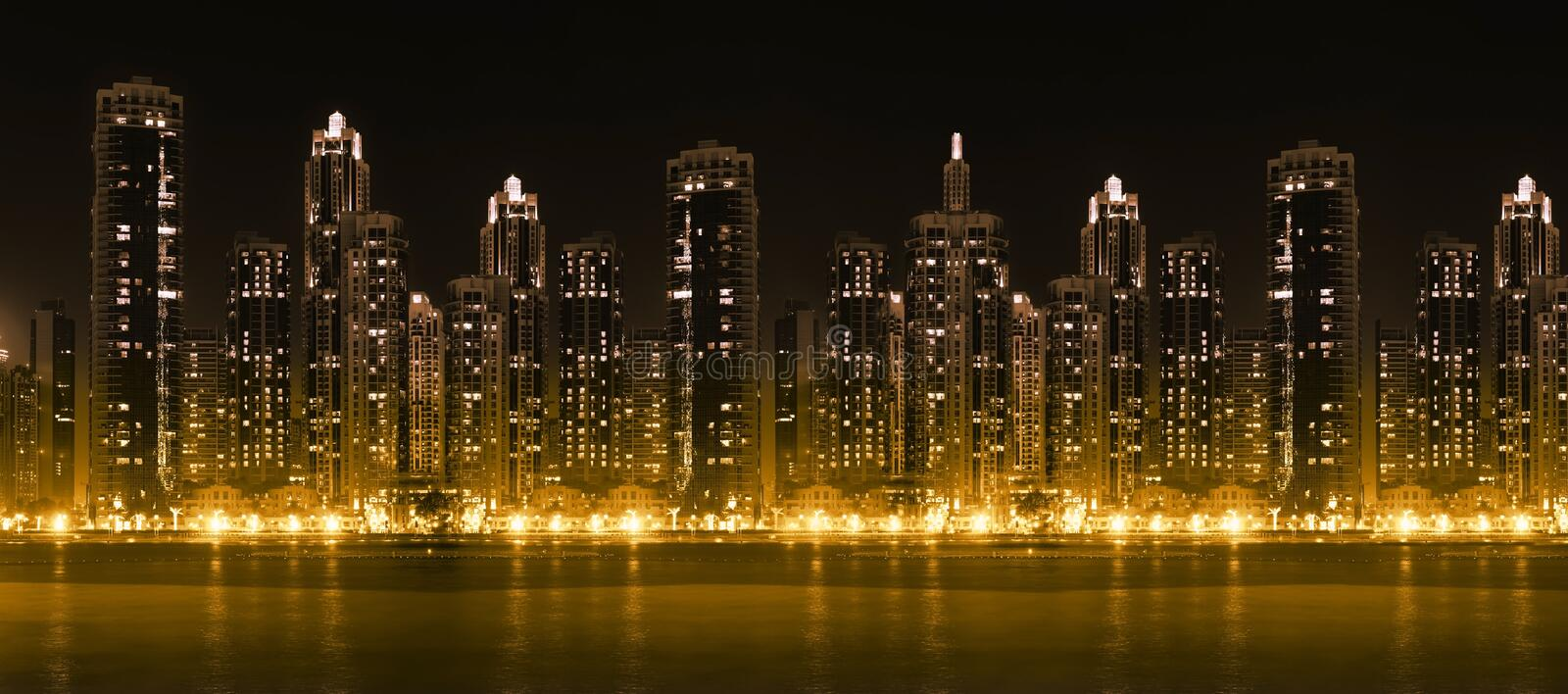 Modern city skyline at hight with illuminated skyscrapers. Modern city skyline at night with illuminated skyscrapers over water surface stock image