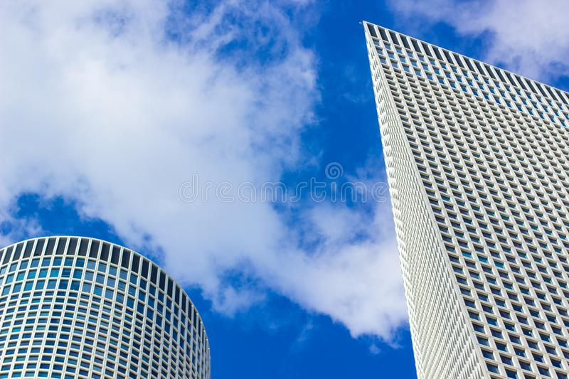 Modern city skyscraper tower buildings exterior facade foreshortening from below on vivid blue sky white fluffy clouds background royalty free stock photos