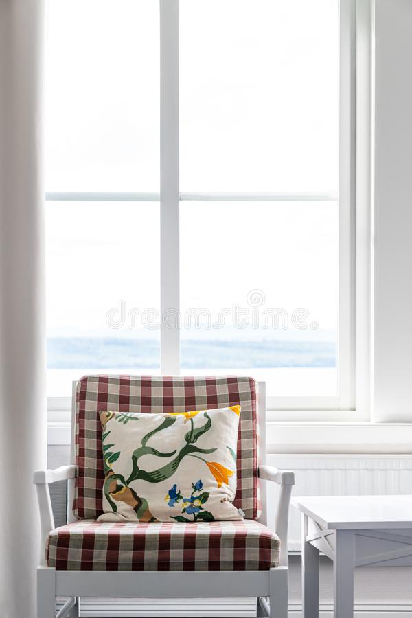 Modern classic furniture. White armchair with checkered cushion and pillow in front of bright window. royalty free stock images