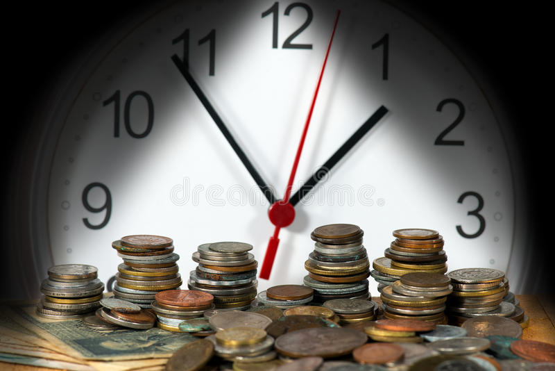 Modern Clock with Old Coins. Detail a modern clock with many old vintage metallic coins. Time is money royalty free stock images