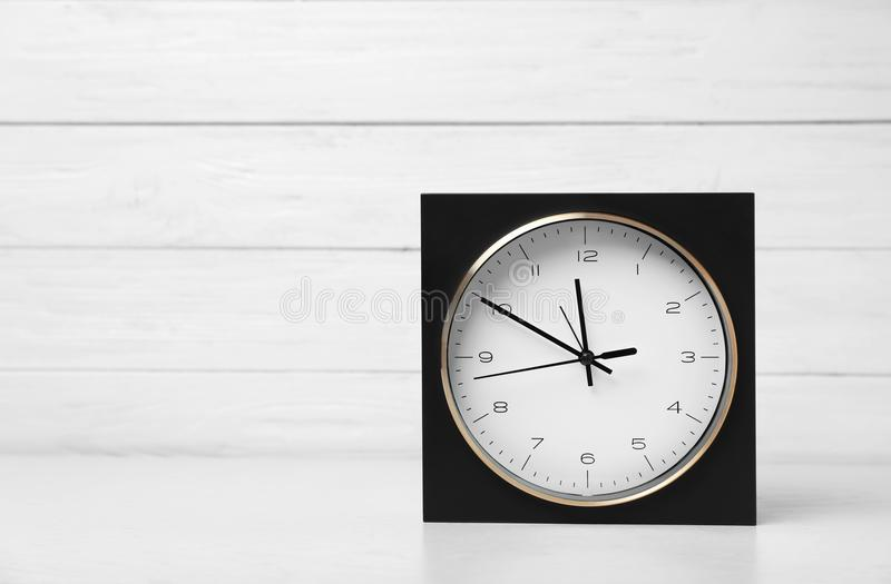 Modern clock on table against light background. Time management royalty free stock image