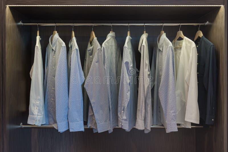Modern closet with clothes hanging. On rail, wooden wardrobe, walk in closet interior design stock photos
